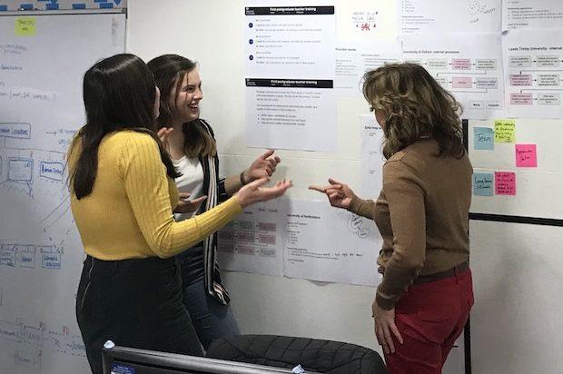 A team discuss their work at their team wall