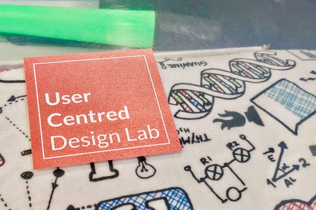 "Coral coloured sticker saying ""user centred design lab"" on a clear plastic stationery box"