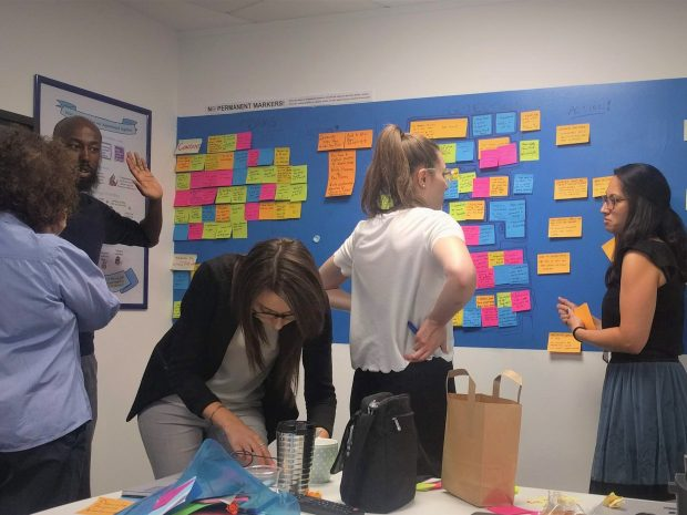 Photo of 5 people talking in front of a colourful 'agile' wall with postits on
