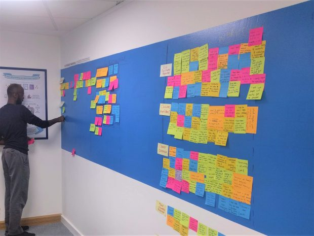A team member putting post-its on an 'agile' wall