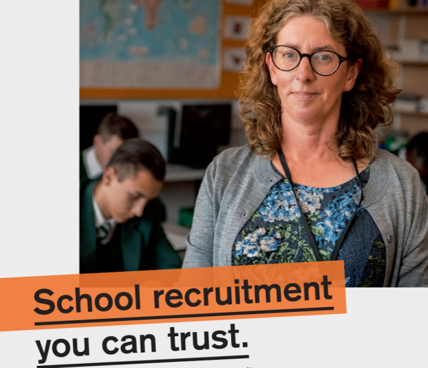 Teaching Vacancy service poster showing a woman teacher standing looking at the camera with pupils in uniform studying behind her