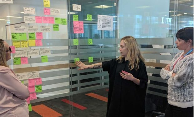 three female members of the team plotting out post-it notes on a glass wall