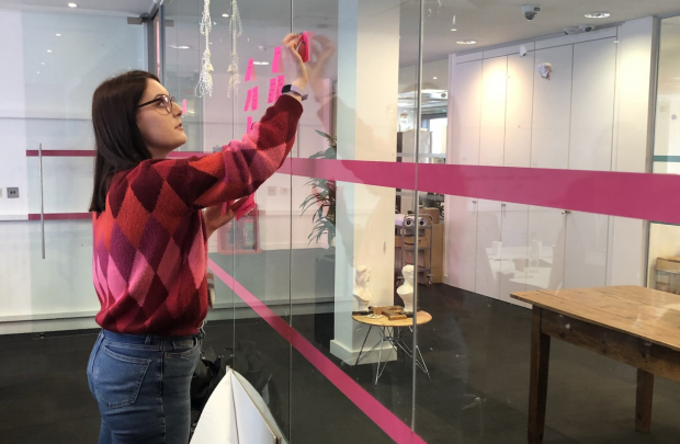 Jessie Fergusson creating an agile wall on a glass panel