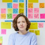 Headshot of Isabelle Andrews in front of an agile wall with postits on