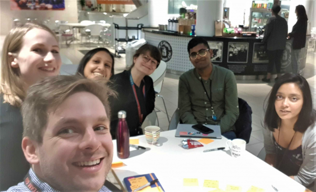 A group of 5 DfE product managers smiling at the camera while sitting down at a table during their product crit meeting
