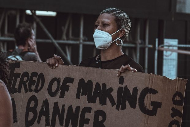 Image of a black woman wearing a face mask and holding a sign which reads 'Tired of making a banner'