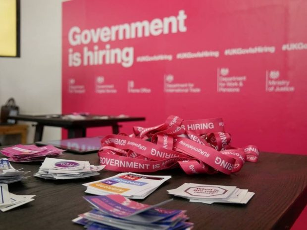 The focus of the image are some lanyards and sticker on a table. They're in front of a pink billboard that reads 'Government is hiring'