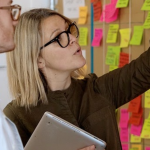 A blonde woman with glasses looking at an agile wall covered in colourful post-it notes