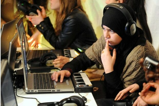 School girl working at a computer during a music class